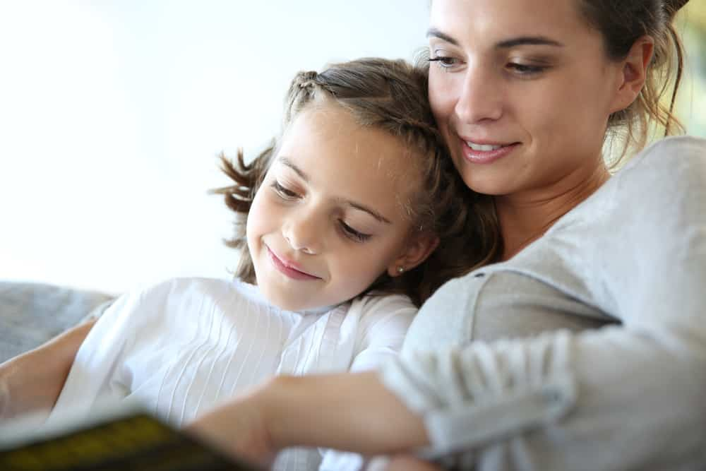 This is a close look at a mother and daughter reading a book on the couch.