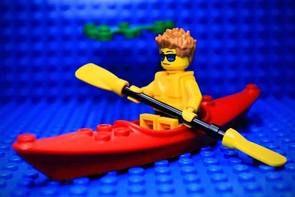 A lego man on a lego boat rowing on lego water.