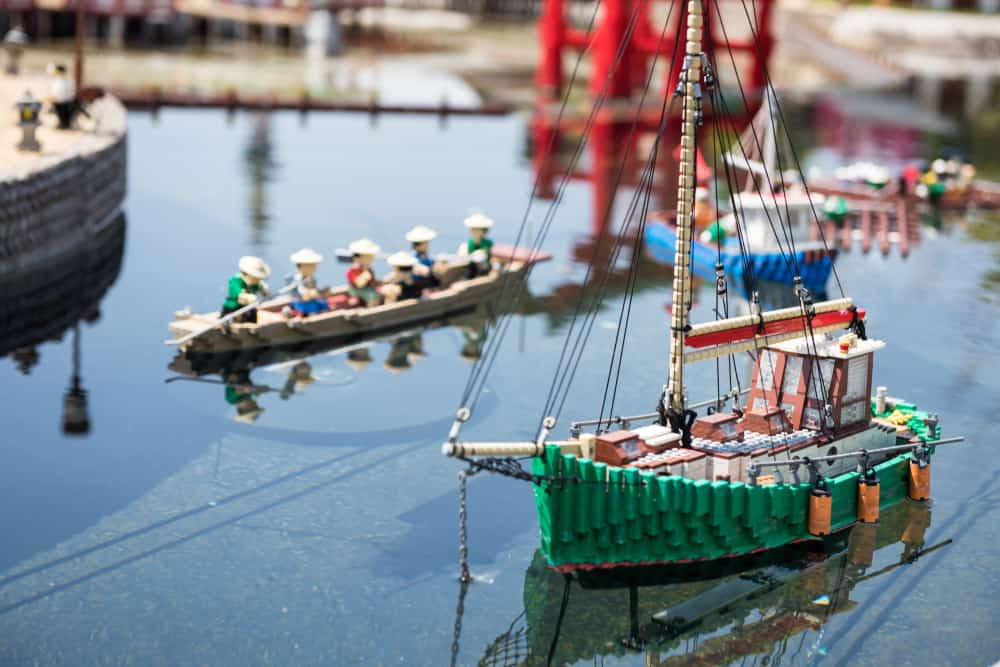 These are various boats made of lego floating on water.