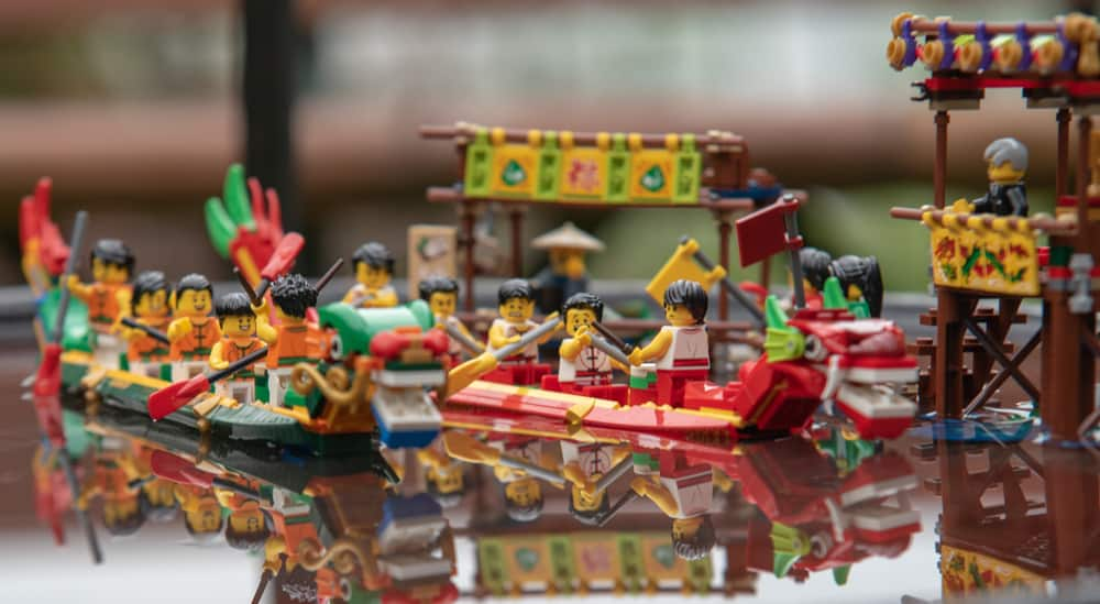 This is a close look at various boats made of lego floating on water.