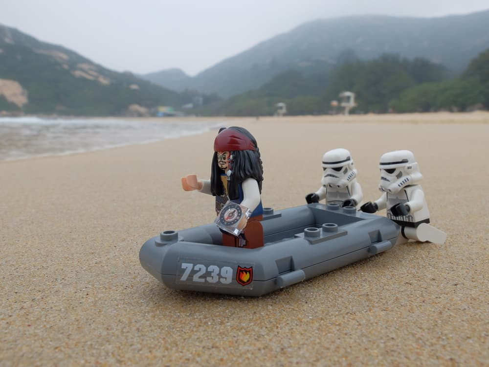 This is a close look at lego Jack Sparrow, lego storm troopers and a lego lifeboat on a beach.