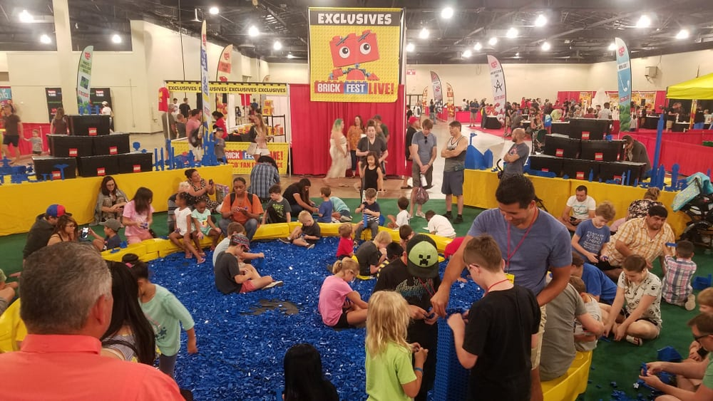 This is a close look at Legoland with lots of children playing with lego pieces.