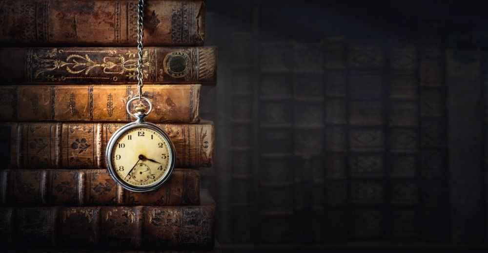 A close look at stack of vintage books along with a chain pocket watch.
