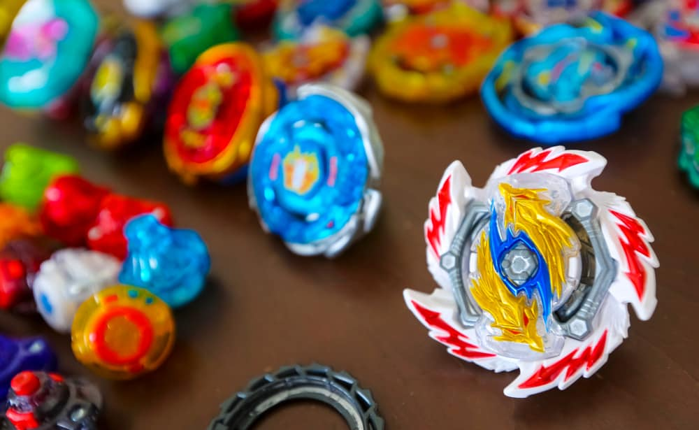 This is a close look at various colorful Beyblade toys on a table.
