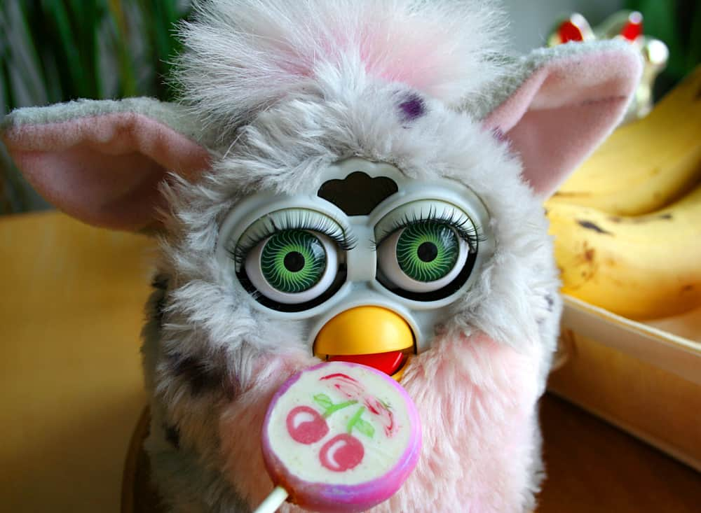 This is a close look at a Furby toy with large eyes and thick fur.
