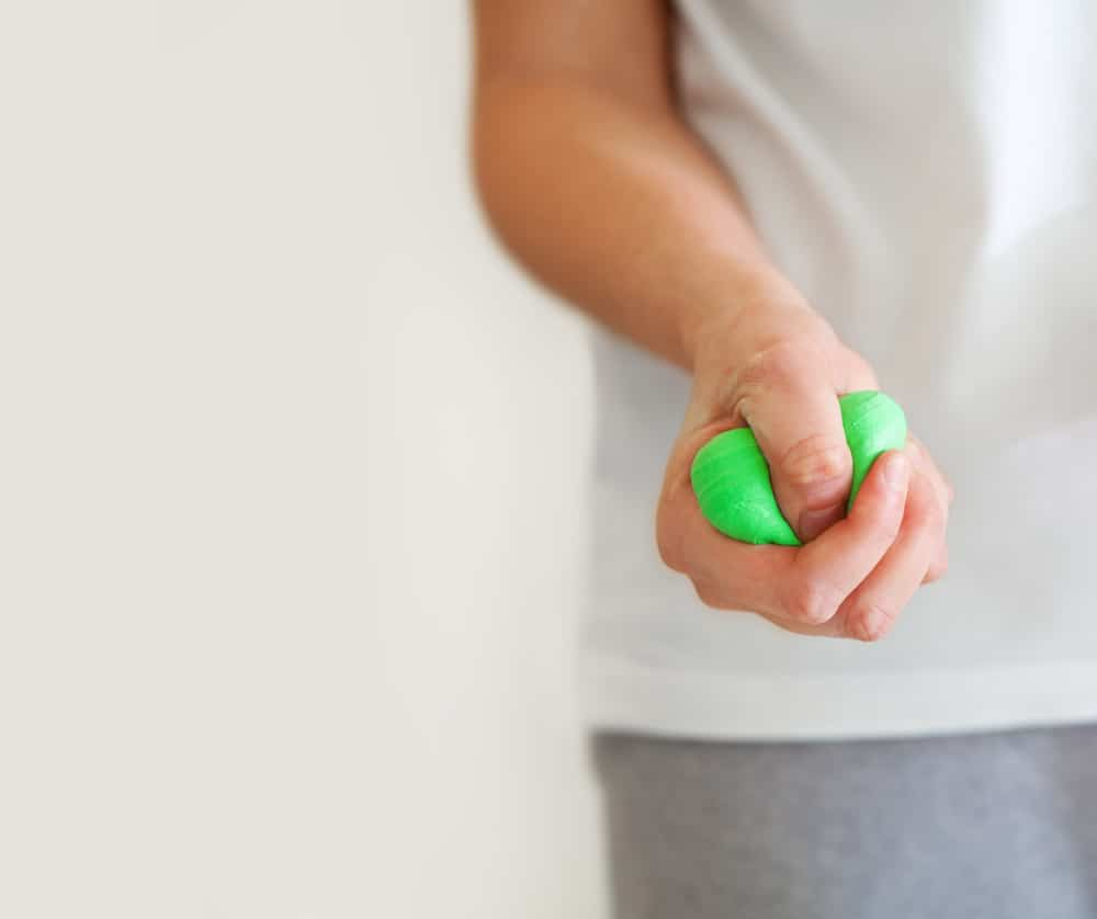 A woman playing with a green putty slime.