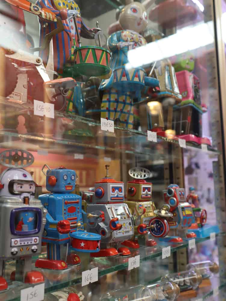 This is a close look at a collection of vintage tin toys on display with price tags.