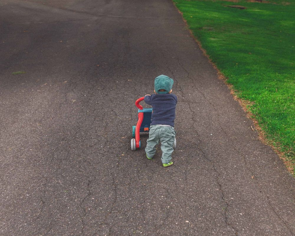 Baby wlaking using a walker for support.