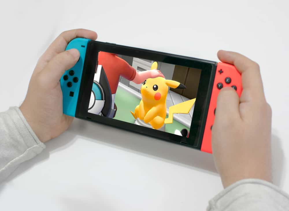 Young man playing pokémon let's go pikachu on a nintendo switch red and blue.