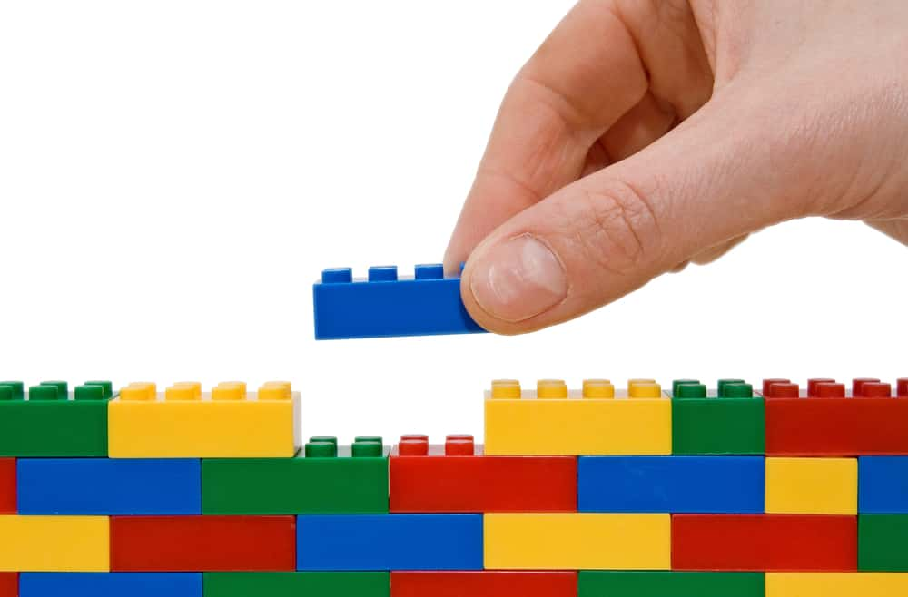 This is a close look at someone building with pieces of colorful Lego blocks.