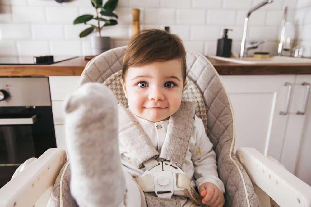 A baby sitting on a high chair at the kitchen.