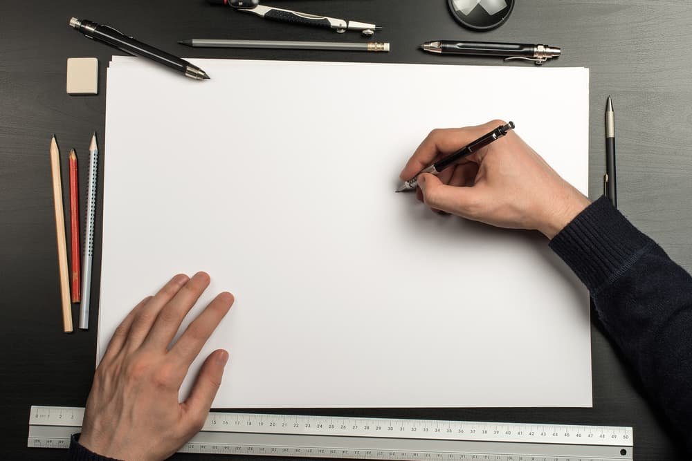 A close look at a person about to draw on paper with accessories on the side.
