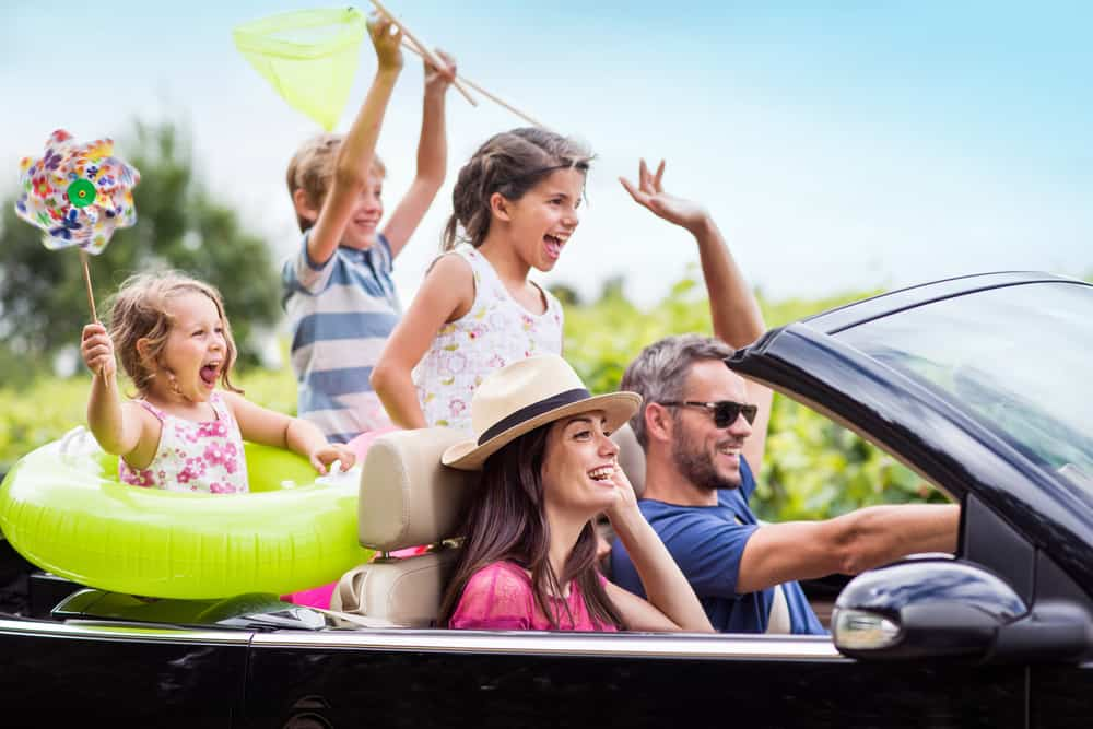 A happy family riding on a convertible car on a road trip.