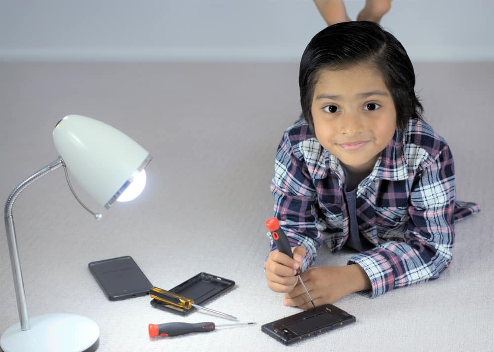 A close look at a kid fixing a mobile phone with a screw driver.