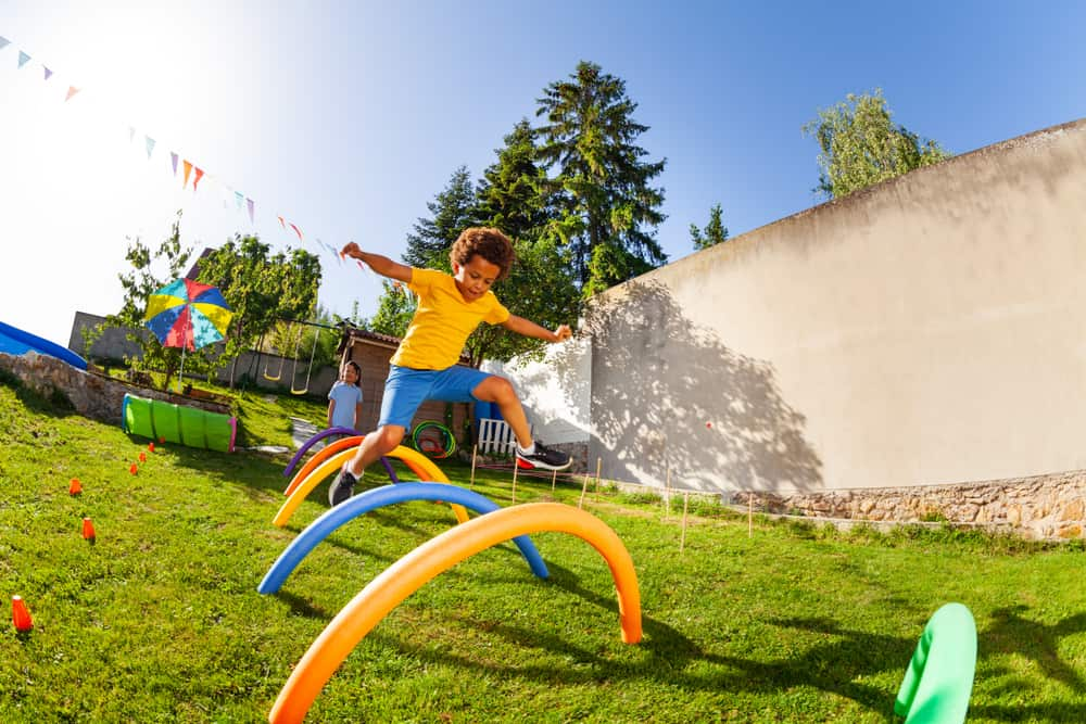 A kid playing on the obstacle course with colorful structures.