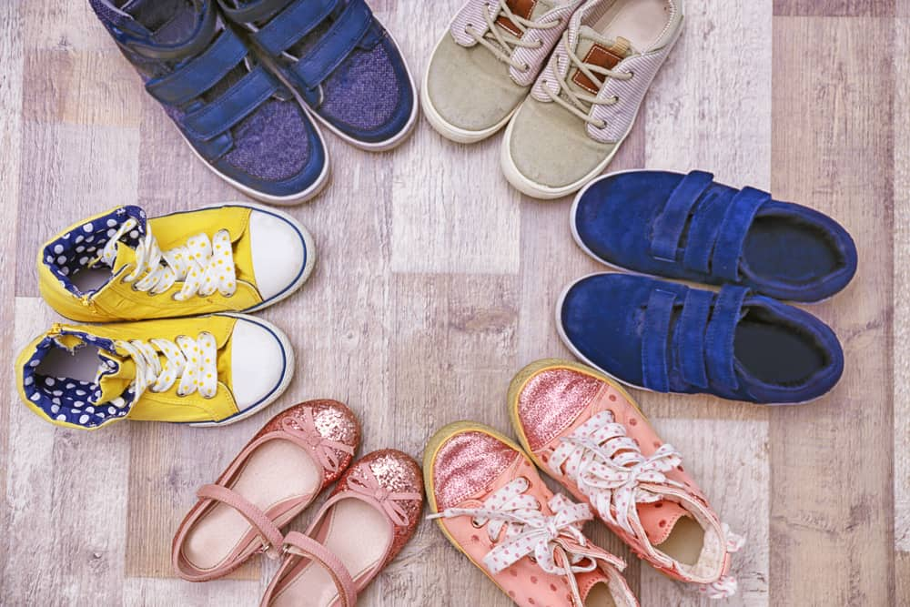 Various colorful kids shoes on the floor.