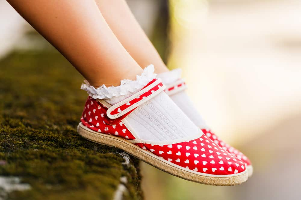 A close look at a girl's red patterned dress shoes.