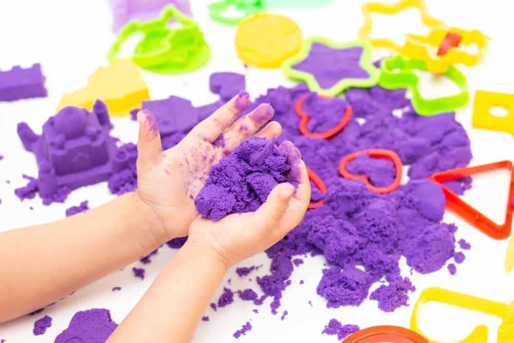 A kid playing with purple kinetic sand.