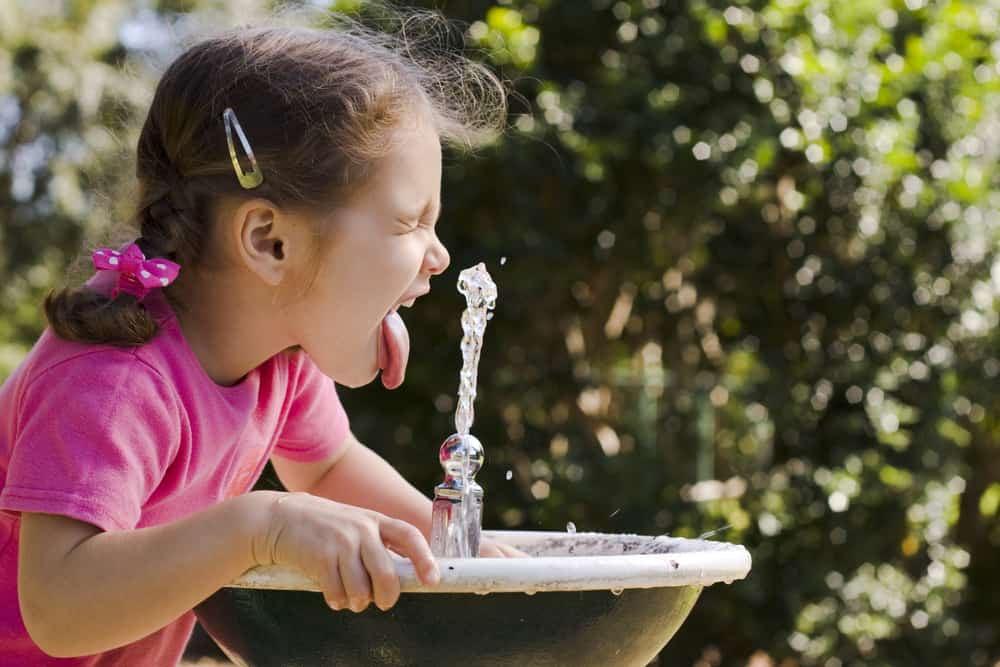 A girl drinking from a water fountain.