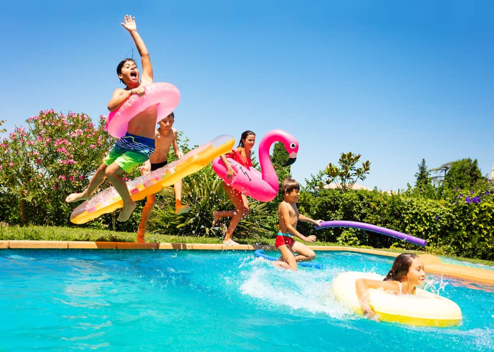 Kids jumping on the pool with inflatables.