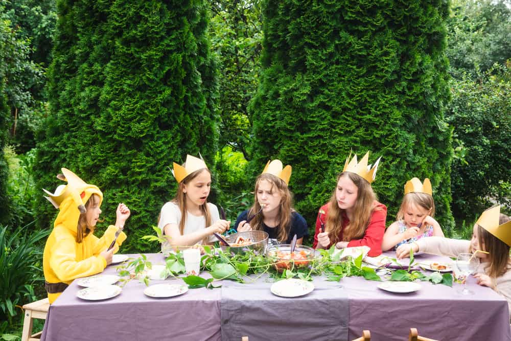 A group of kids on a backyard luncheon party.