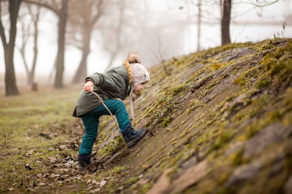 A kid playing on a mossy little hill with sticks.