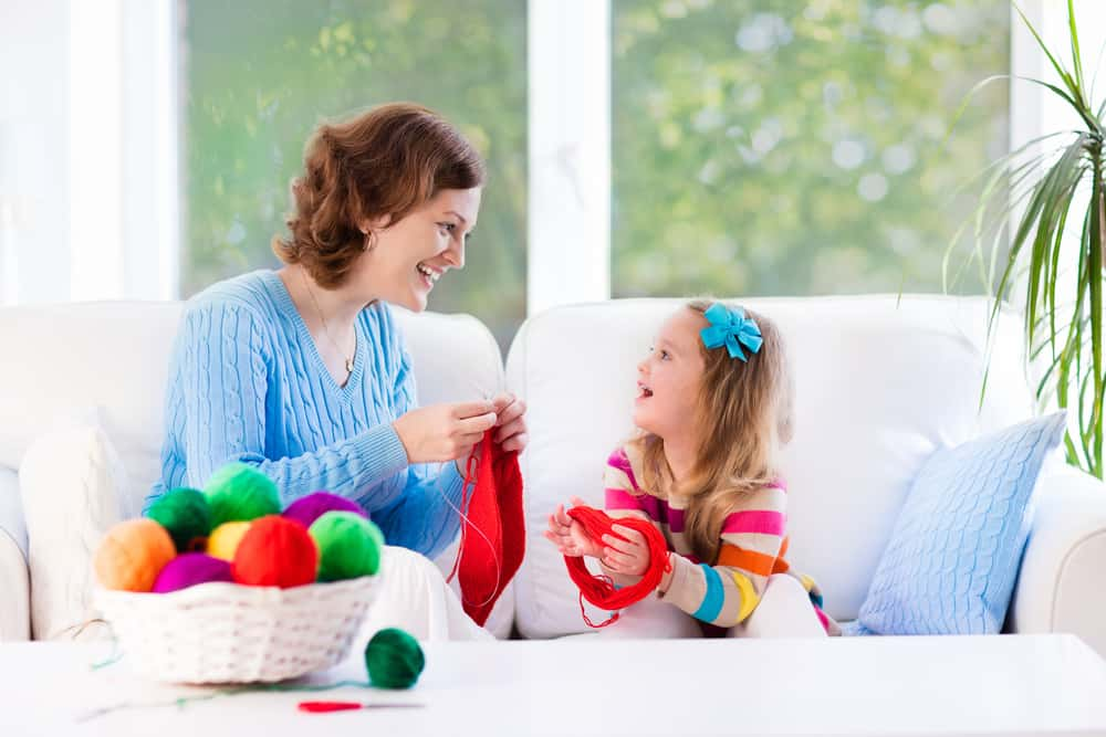 A mother and daughter knitting together in the living room.