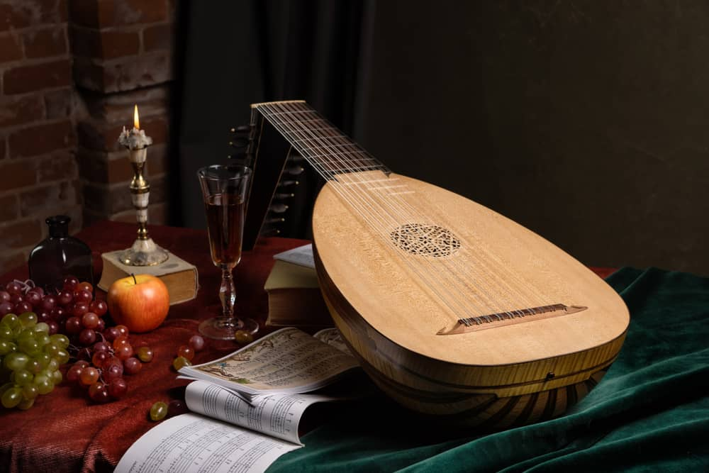 This is a Renaissance style lute on a table with grapes.