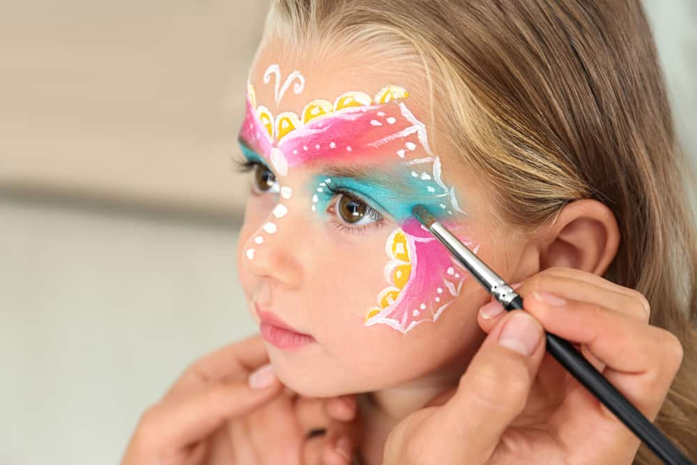 A little girl having her face painted.