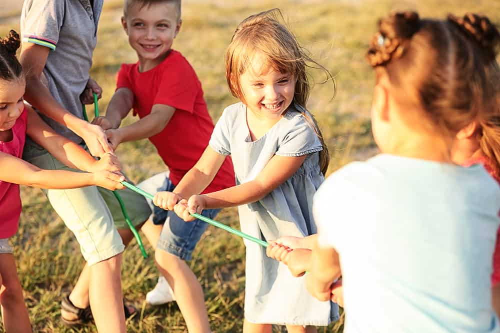 A group of kids playing tug of war.