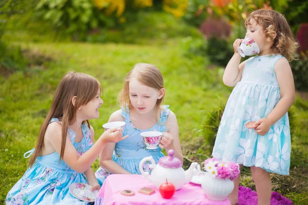 Girls having a tea party in the backyard.