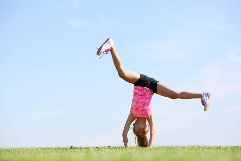 A girl in the middle of a cartwheel.
