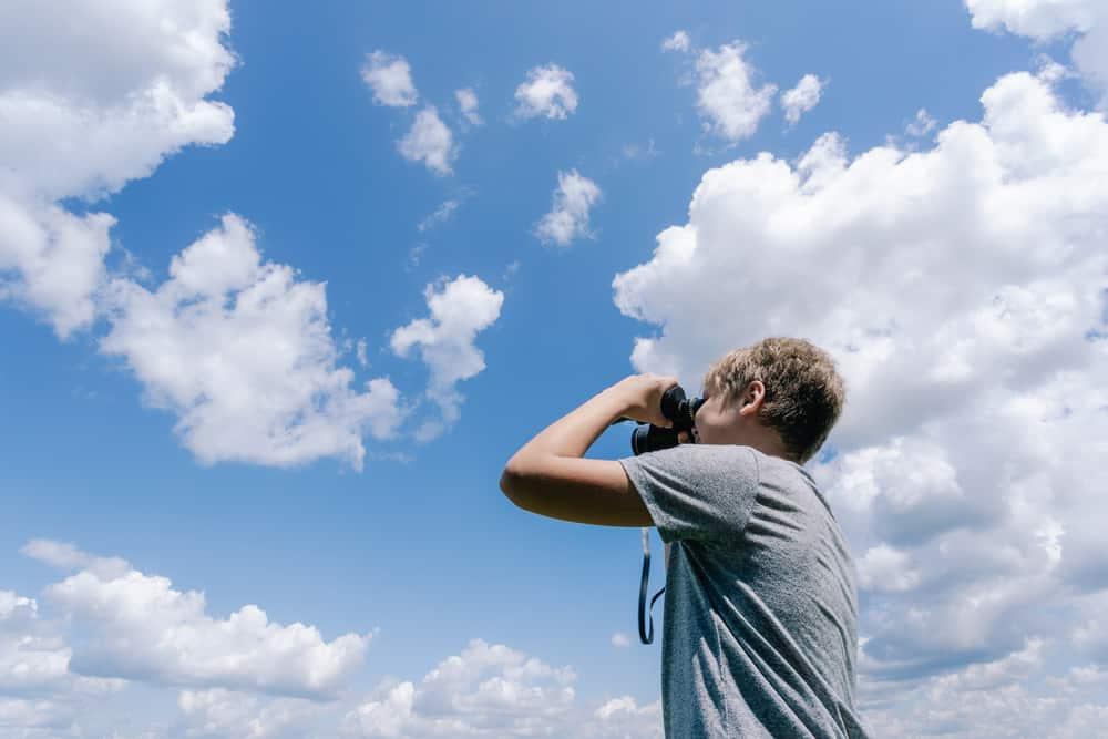 A boy taking pictures of clouds with his camera.