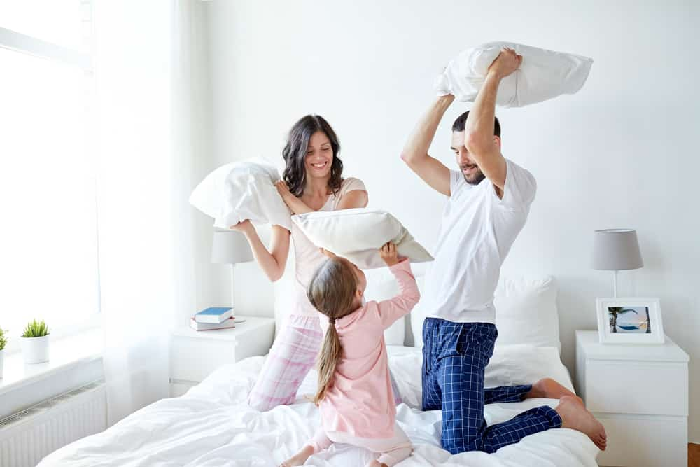 A family playing pillow fight together in the bedroom.