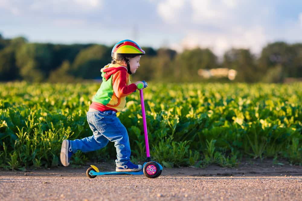 A kid playing on a plastic scooter.