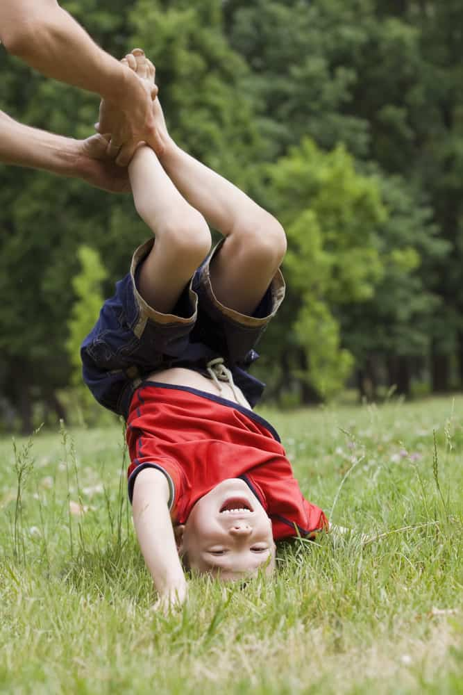 A boy doing a hand stand with support.