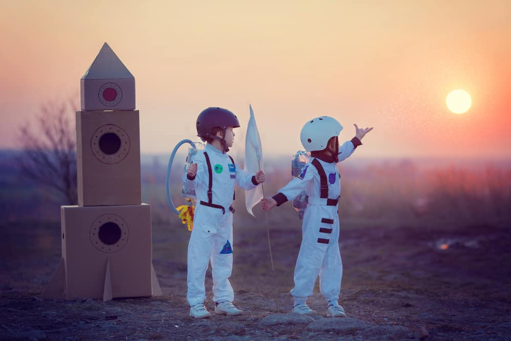 Kids playing with a cardboard rocket.