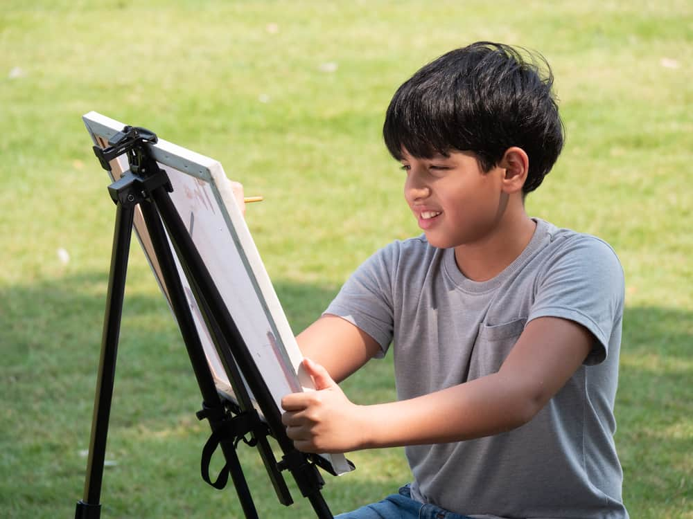 A boy painting on canvas in the backyard.