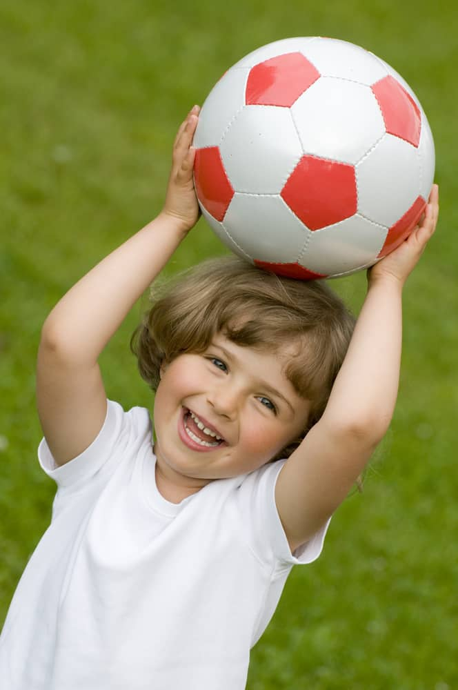 A little girl playing with a soccer ball.