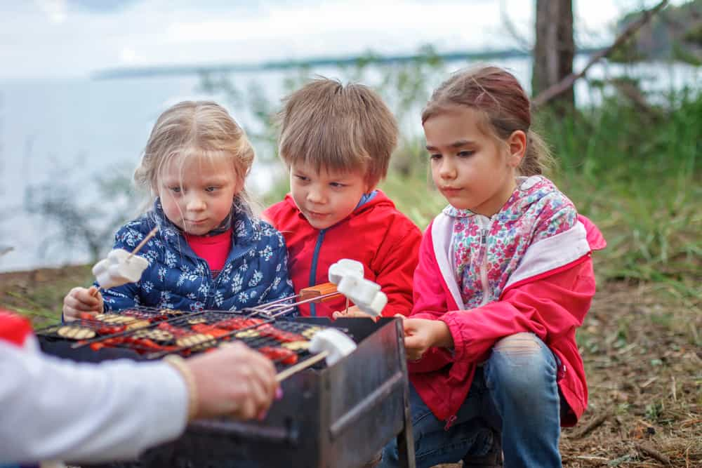 A group of kids toasting marshmallows.