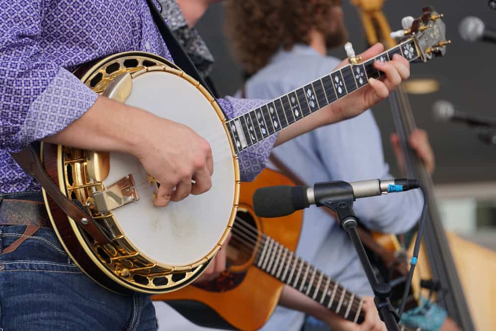 A close look at a banjo being played with a band.