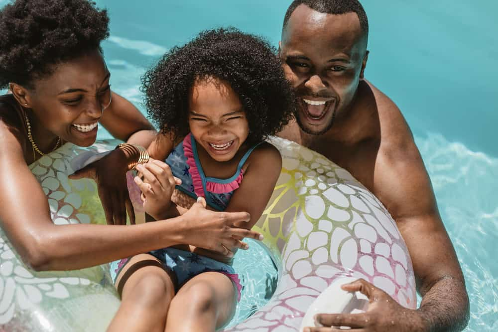 This is a close look at a family of three playing in the pool.
