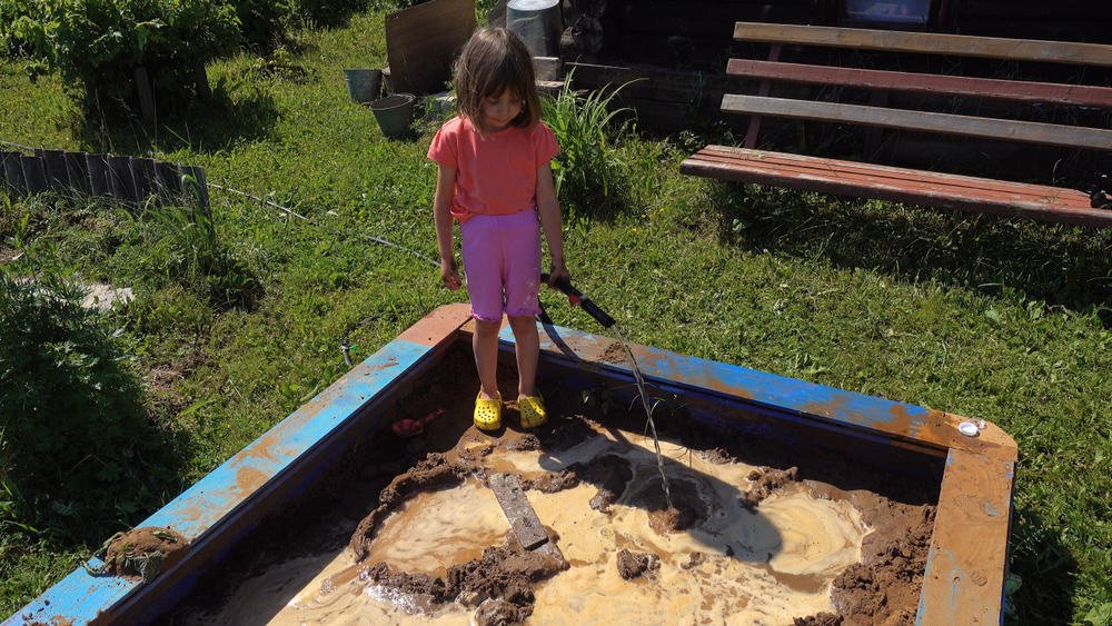 A girl trying to make a mud castle.