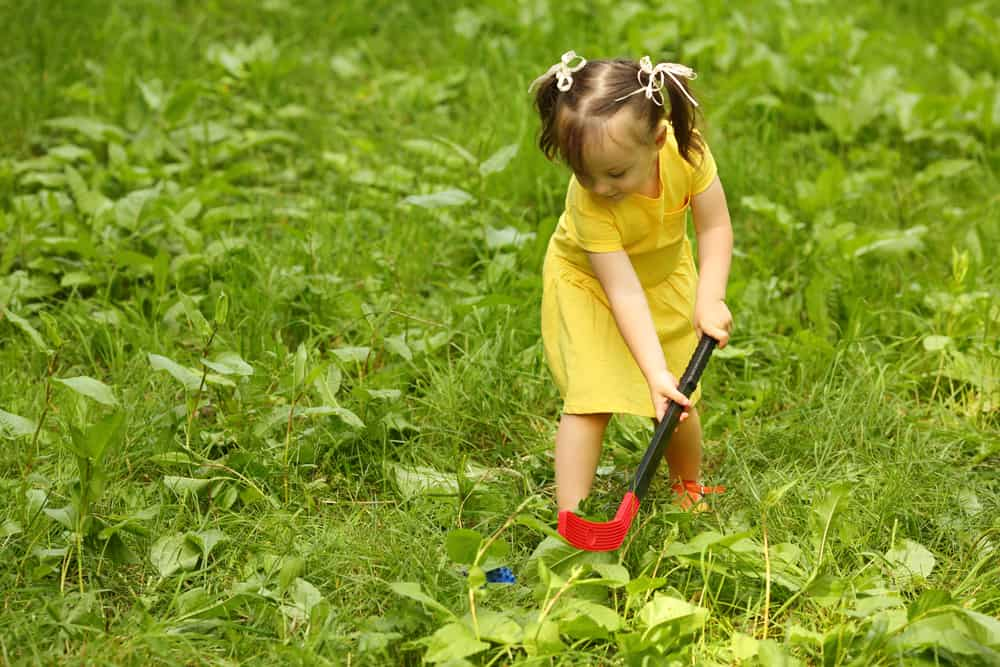 A little girl playing field hockey.