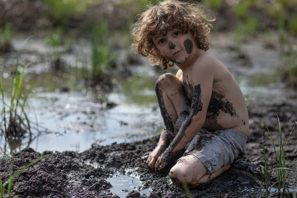 A boy playing with mud.