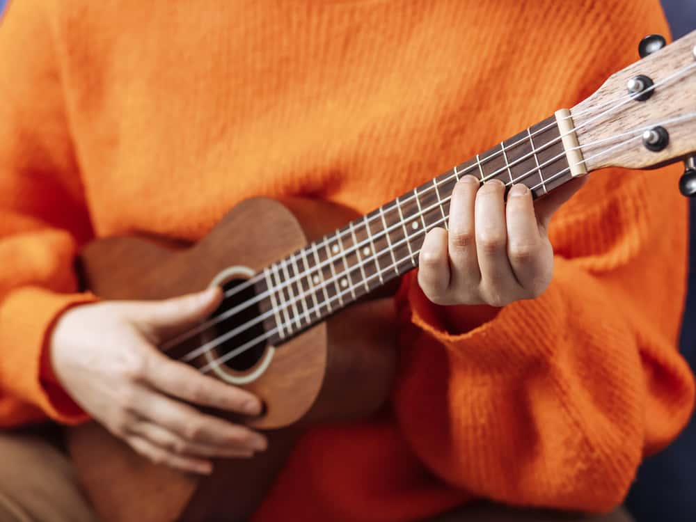 A close look at a girl playing the ukelele.