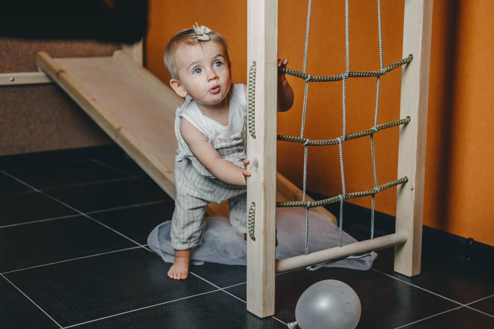 A toddler playing in an indoor play gym.