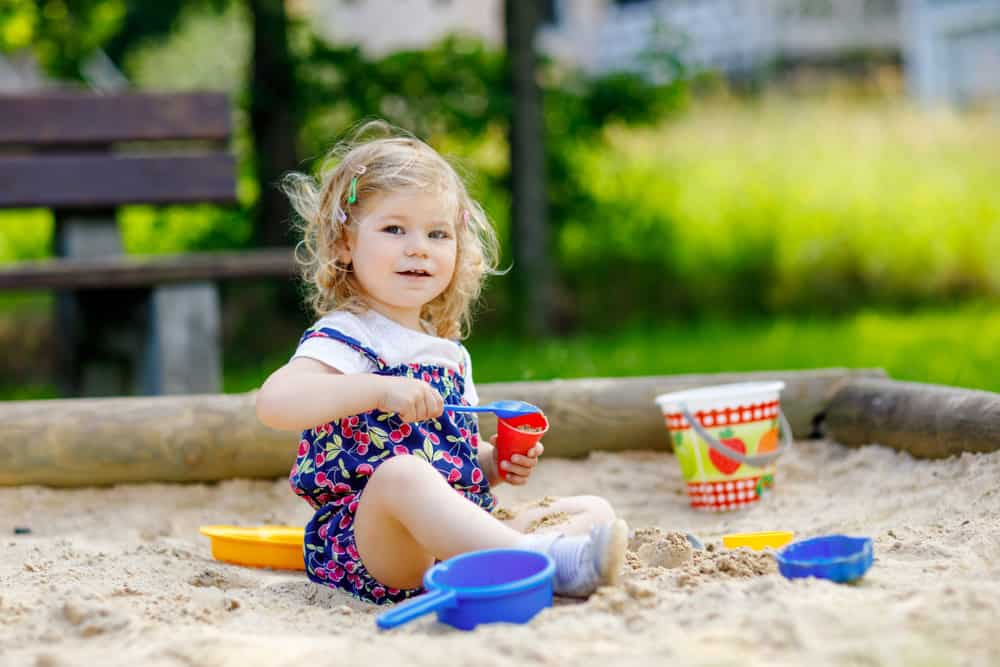 A toddle paying on the sand box with plastic toys.