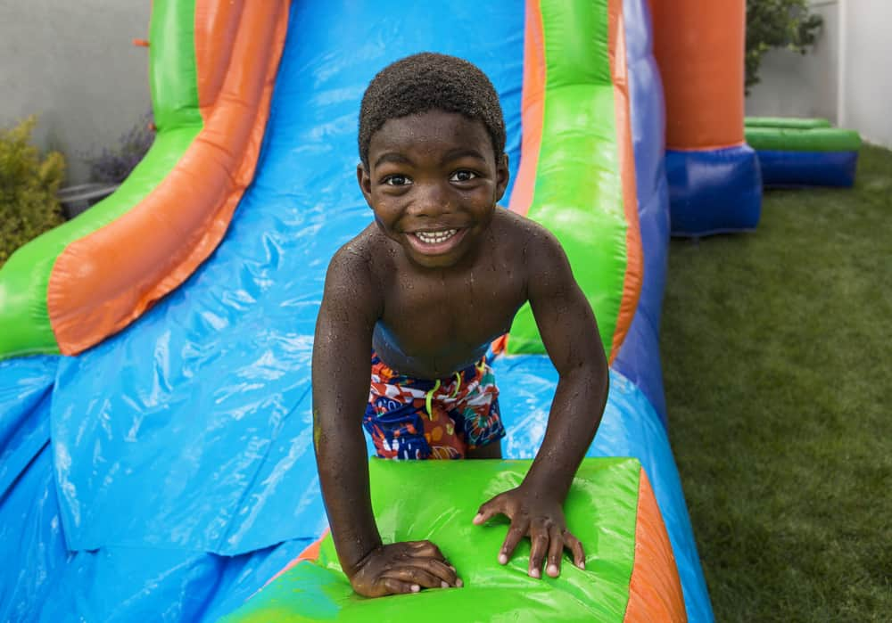 A boy playing on an inflatable bounce slide house.