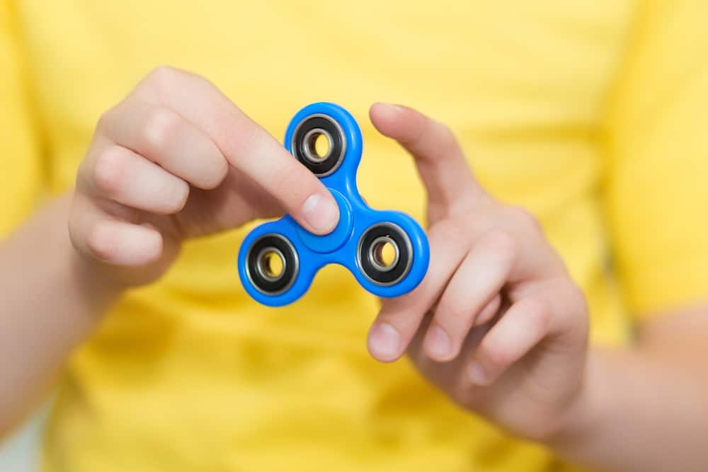 A kid playing with a blue fidget spinner.